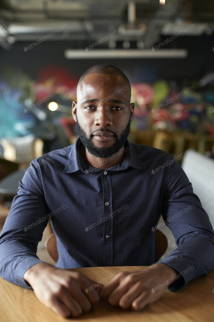Mid adult black male creative sitting at a table in an office cafe looking to camera, close up