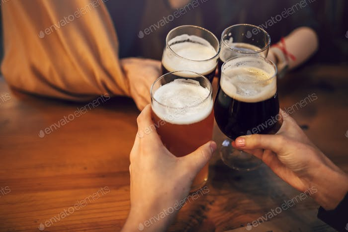 hands of people holding beer and cheering in brewery pub