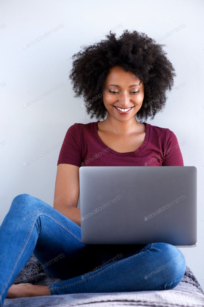 happy african woman sitting at home using laptop computer