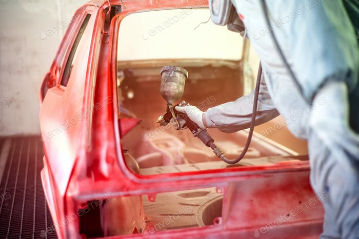 paint engineer working on red car in painting booth