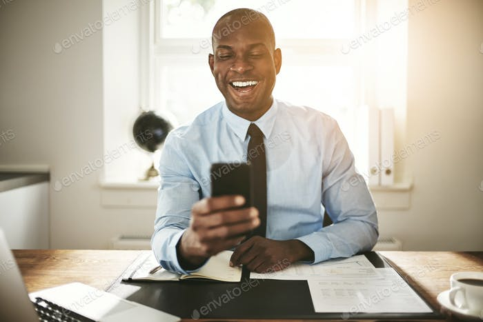 Smiling young businessman laughing at a cellphone message