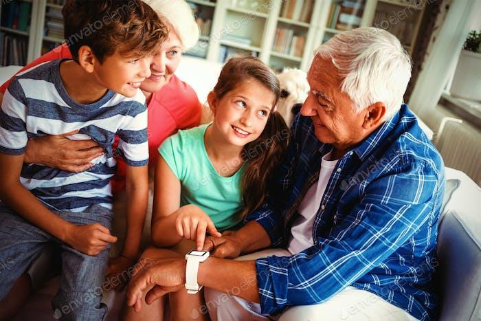 Grandparents and grandchildren looking at smartwatch in living room