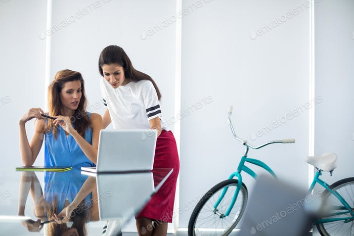 Executives using graphic tablet and laptop