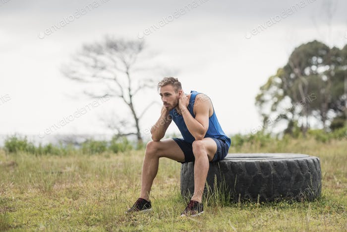 Tired fit man sitting on tire