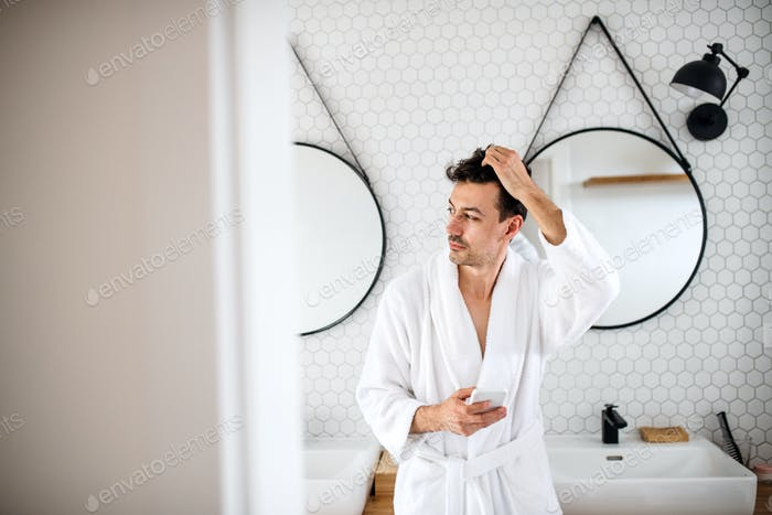 Young man with smartphone in the bathroom in the morning