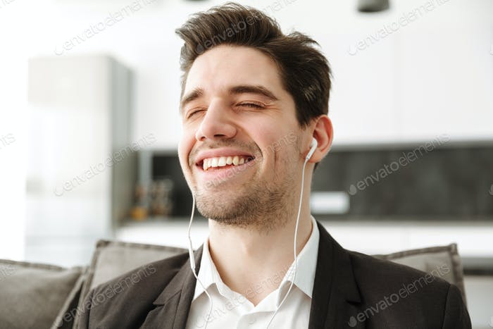 Cheerful young businessman in home listening music
