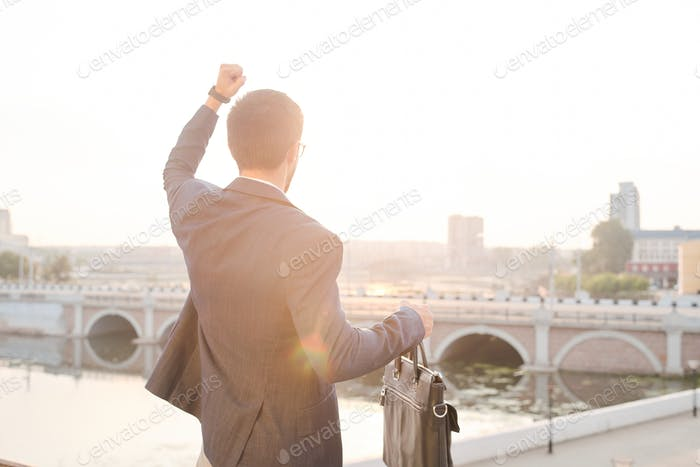 Rear view of young winning businessman with leather handbag expressing triumph