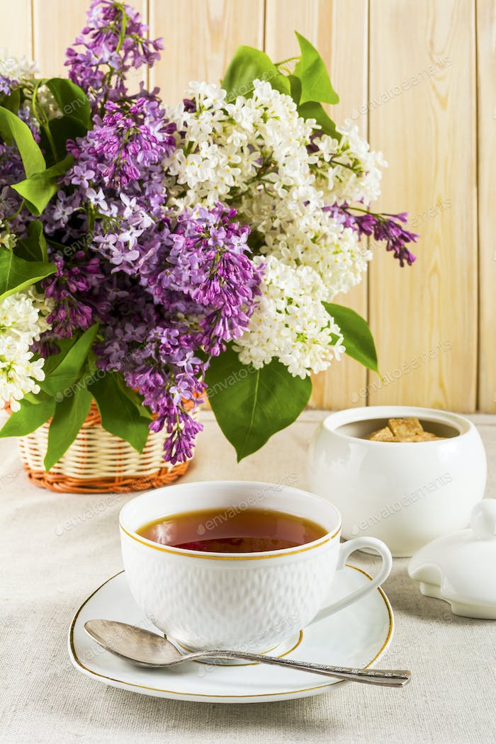 Cup of tea and branch of lilac flower on linen tablecloth