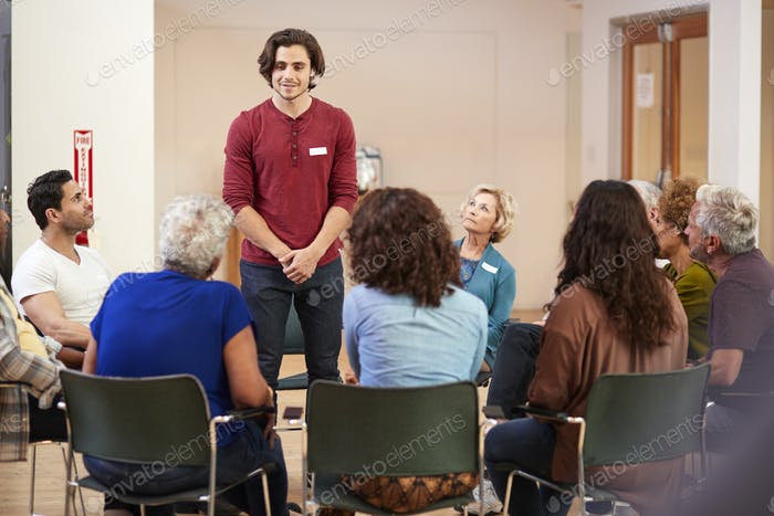 Man Standing To Address Self Help Therapy Group Meeting In Community Center