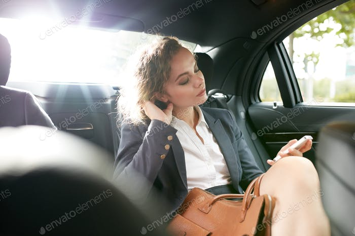 Female entrepreneur travelling to work in a luxury car