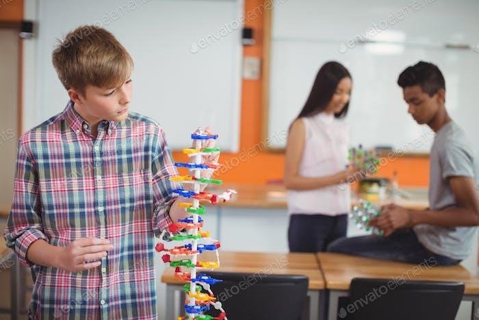 Schoolboy examining the molecule model in laboratory