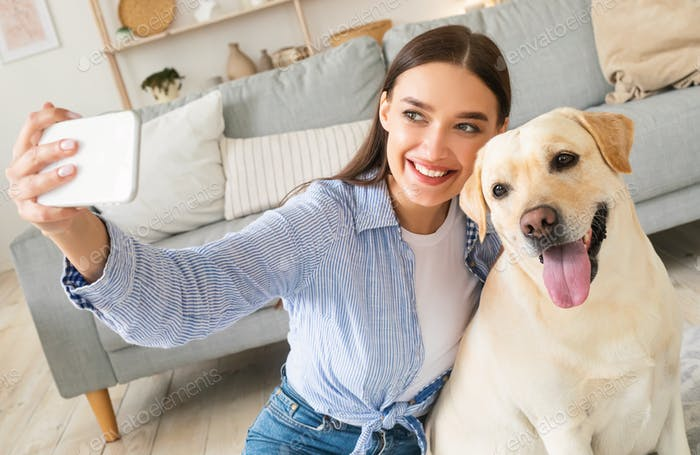 Young woman with her dog taking selfportrait