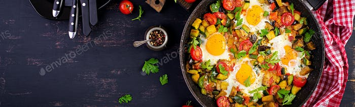 Late breakfast - fried eggs with vegetables. Shakshuka. Arabic c