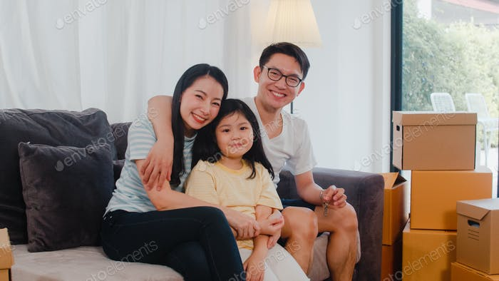 Happy Asian young family homeowners bought new house.