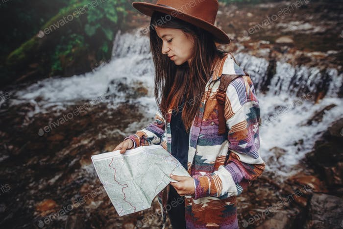 stylish traveler girl in hat looking at waterfall, exploring woods