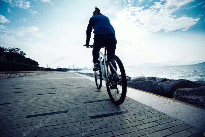 Riding mountain bike on sunrise coast