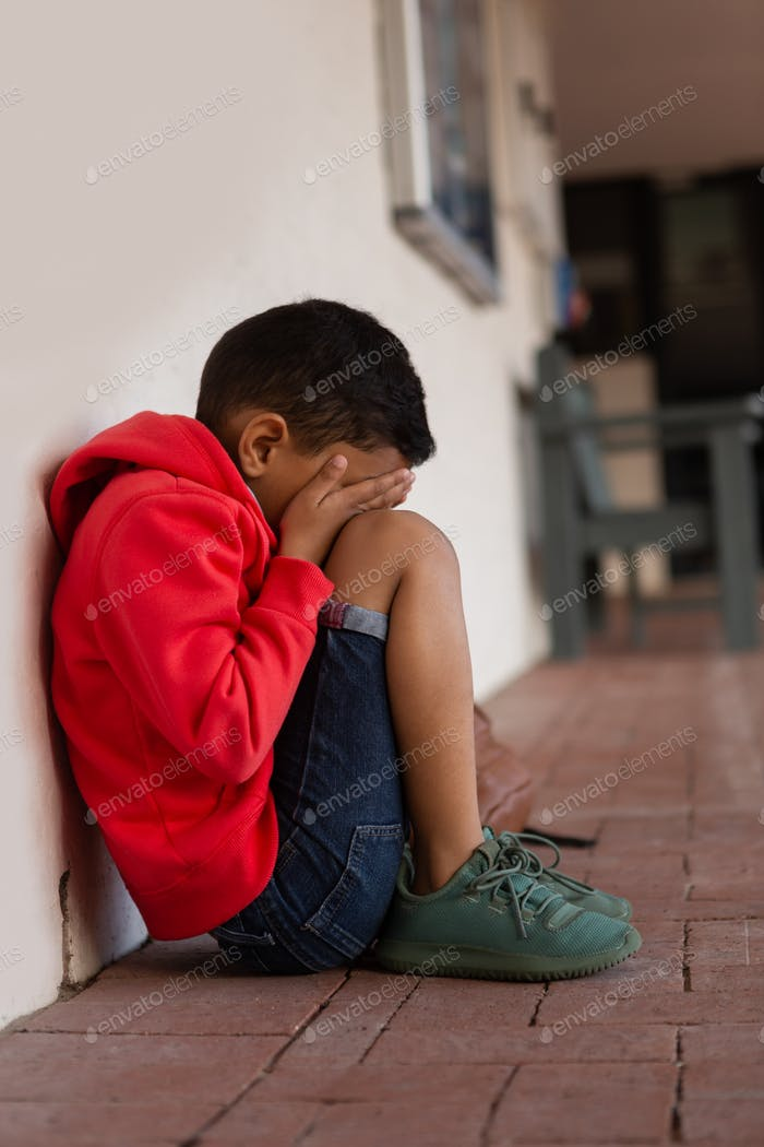 Side view of sad mixed-race schoolboy sitting alone on floor in corridor at elementary school
