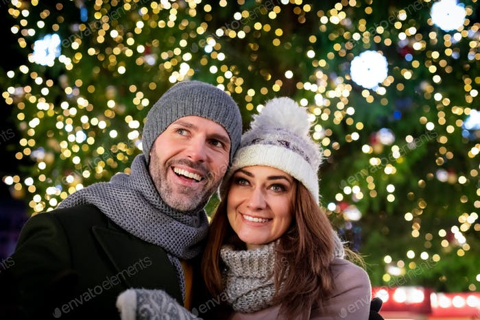 The couple spends the evening at a Christmas market full of light decorations