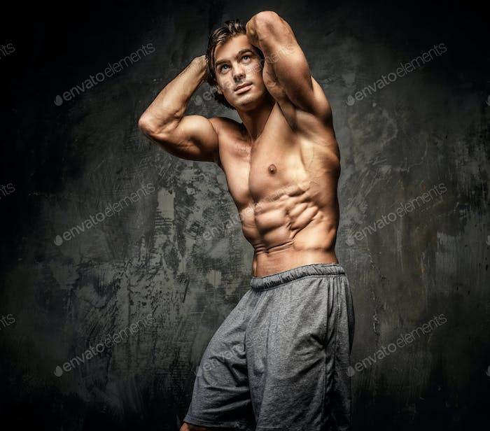 Shirtless muscular guy posing in studio.