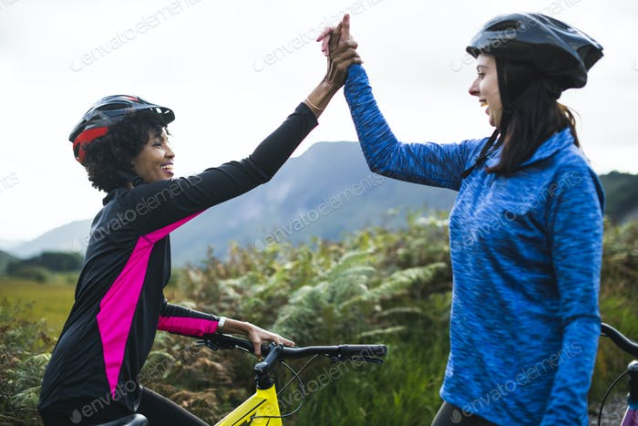 Female cyclists giving a high five