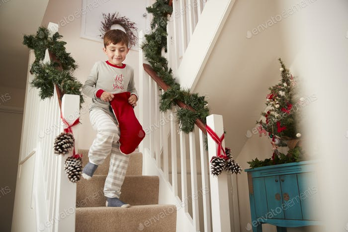 Excited Boy Wearing Pajamas Running Down Stairs Holding Stocking On Christmas Morning