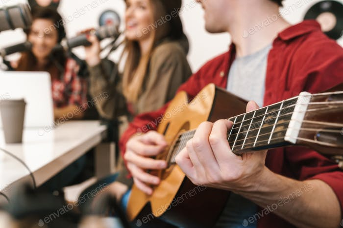 Image of young happy caucasian people performing at radio program