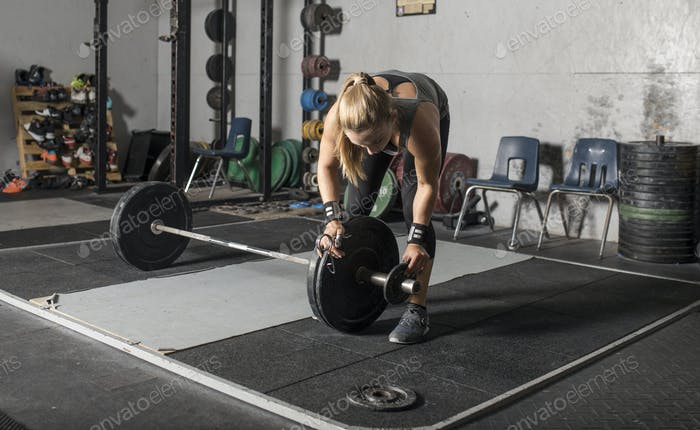 Female weight lifter loading weights onto barbell.