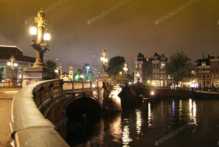 Bridge over the Amstel river at night in Amsterdam