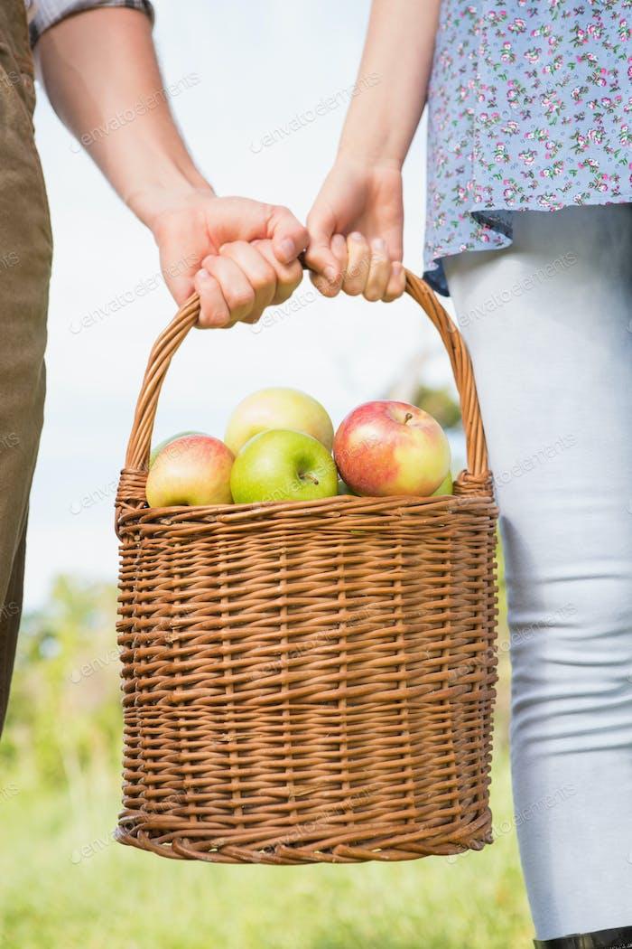 Paar halten Korb mit Äpfeln an einem sonnigen Tag