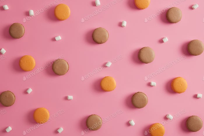 Two colored fresh french macaroons with marshmallow isolated over rosy background. Tasty dessert for