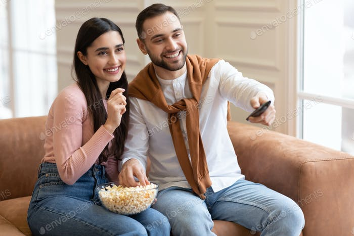 Arab Couple Watching Movie On TV Eating Popcorn At Home