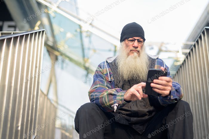 Mature bearded hipster man using phone while sitting at footbridge in the city