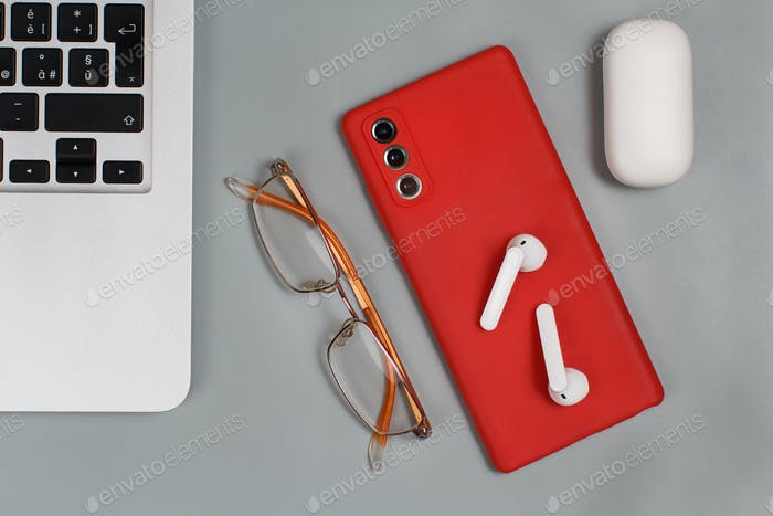 Red Mobile phone, earphones and glasses near laptop