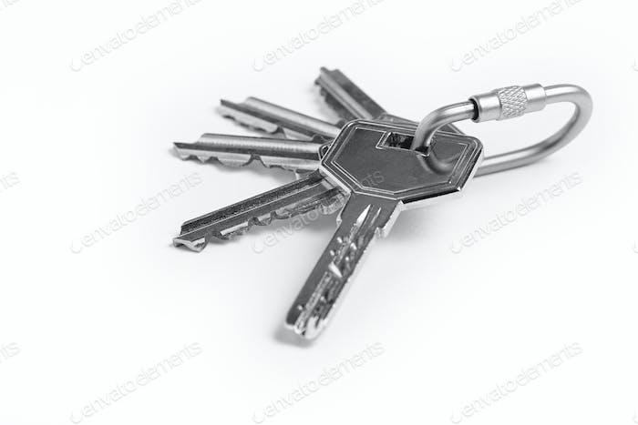 Schlüsselanhänger mit Schlüsseln über weißem Hintergrund. Mieten, kaufen