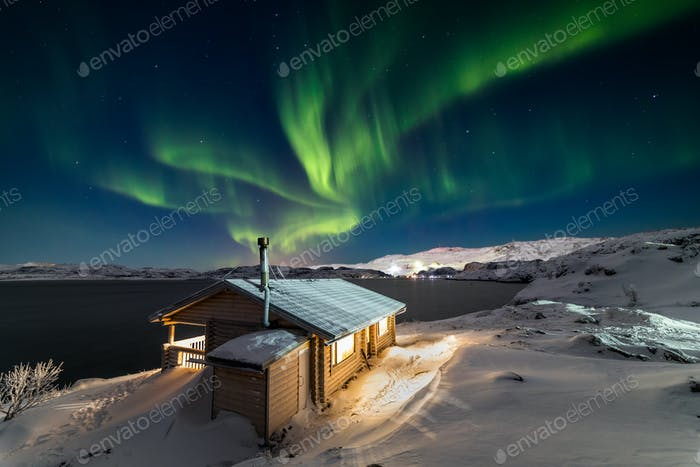 Wooden cottage on the background of the Northern Lights at night