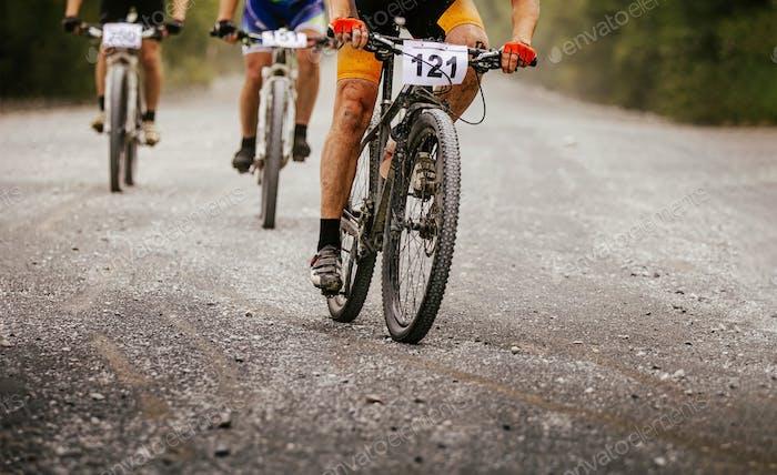 three cyclists riders on mountain bikes