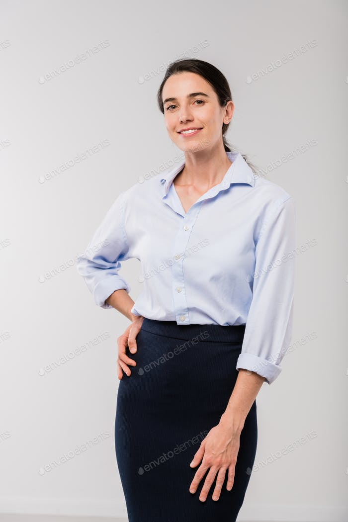 Happy young elegant businesswoman in white shirt looking at you in isolation