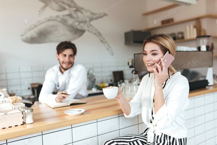 Cheerful girl with cup of coffee happily talking on her mobile phone while barista looking on her