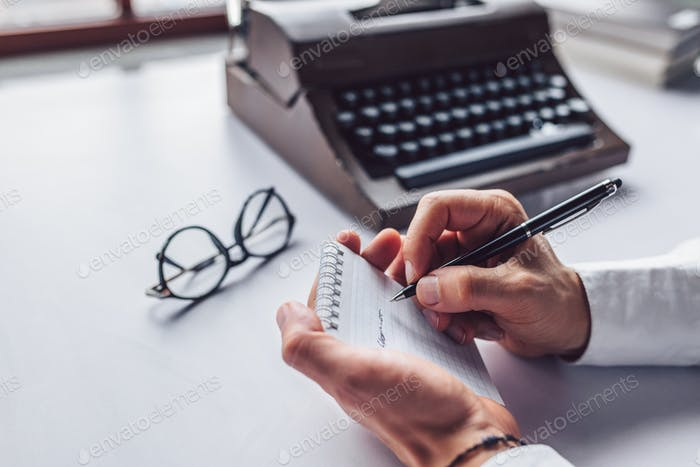 Male hand writing in a notebook