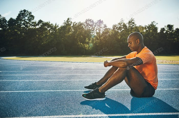 Focused young athlete sitting alone on a running track