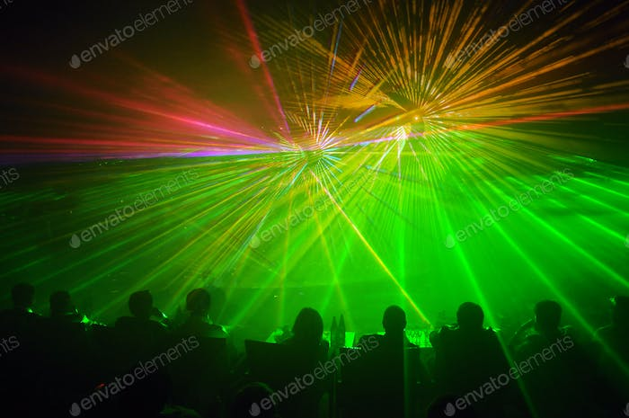 Row of people facing a laser light show
