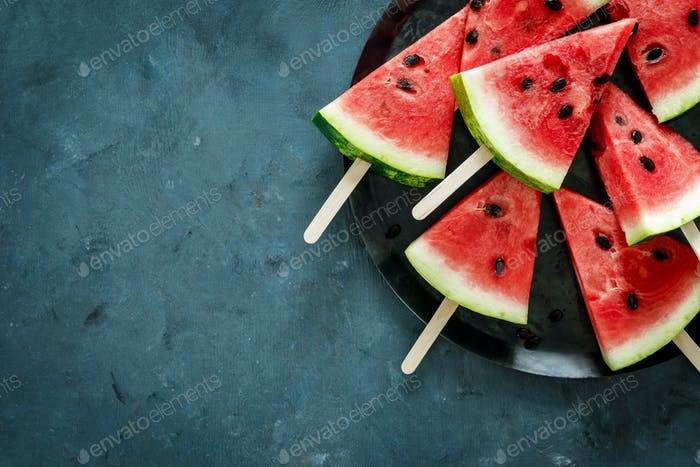 Watermelon slice popsicles on a blue background, top view