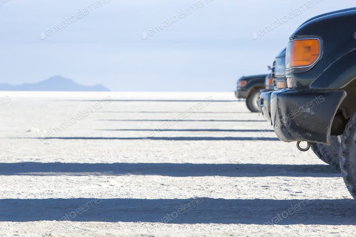 Group of 4x4 sides on the Salar of Uyuni with blue sky