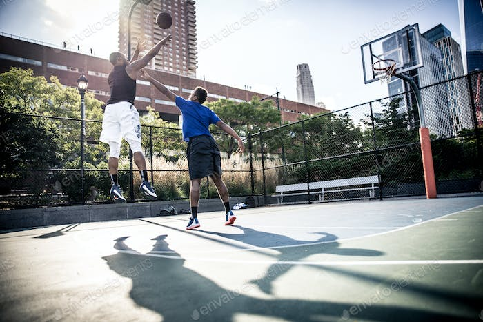 Two street basketball players playing hard on the court