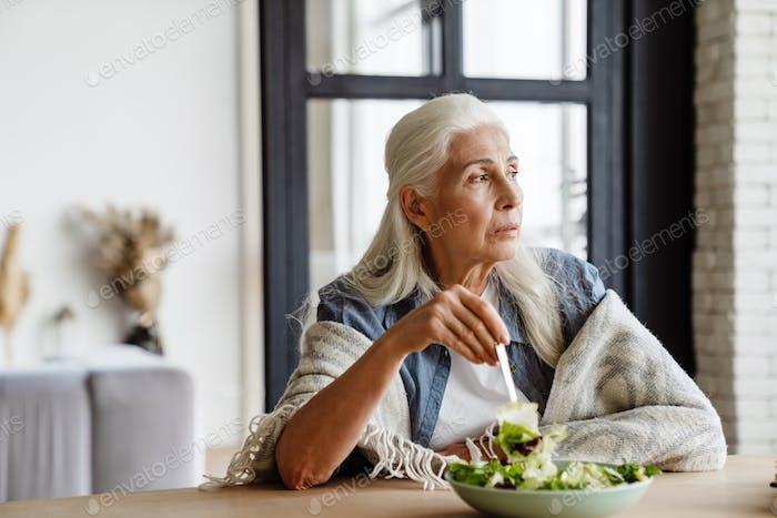 Modern grandmother eating fresh green salad