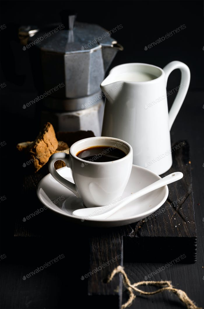 Cup of hot espresso, creamer with milk, cantucci and moka coffee pot on a rustic wooden board