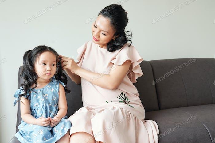 Woman braiding hair of daughter
