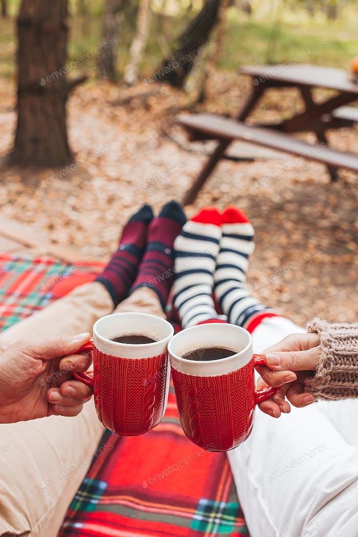 Hot cups of tea in hands in woollen sweater on background of cozy house
