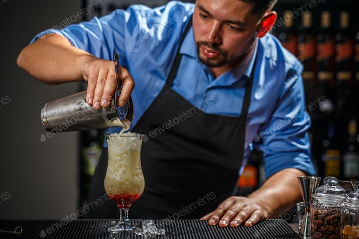 Male bartender is making cocktail