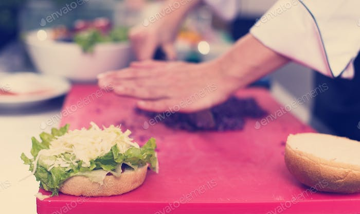 chef hands cutting salad for burger